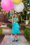 Pretty young girl with big colorful balloons walking in the park near the town - image royalty free stock photo