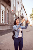 Pretty young girl in narrow street with cell phone Stock Photo