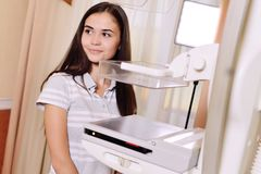 A pretty young girl near a mammographer. An X-ray machine with the help of which breast examinations are performed to prevent or detect tumors and breast stock photography