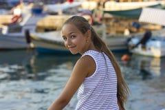 Pretty young girl near the Mediterranean sea looking forward . Antalya, Turkey, marina Royalty Free Stock Image