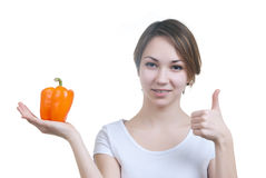 Pretty young girl with orange pepper. Isolated on white Stock Image
