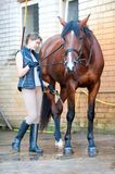 Pretty young girl owner washing her favorite bay horse`s legs. Young teenage girl equestrian washing her lovely chestnut horse`s legs in cool shower. Vibrant Stock Photography