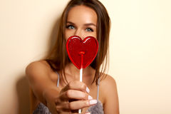 Pretty young girl in a peignoir of chiffon and lace halter with cut and bow in front of hands holding a lollipop in the shape of a Royalty Free Stock Photography