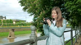 Pretty young girl photographer tourist taking photos with a professional camera near the railing on waterfront, river stock footage