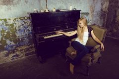 Pretty young girl at piano Royalty Free Stock Image