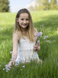 Pretty young girl picking wildflowers. Pretty young girl kneeling in the grass in a rural meadow picking wildflowers and smiling happily at the camera Stock Photo