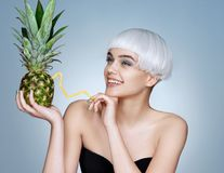 Pretty young girl with pineapple cocktail. royalty free stock photography