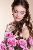 Pretty young girl with pink roses Stock Image