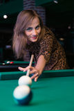 Pretty young girl is playing billiard or pool. At a date in a bar Royalty Free Stock Photos