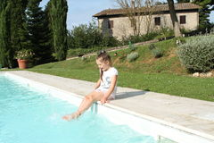 Pretty young girl playing with water at pool's edge Royalty Free Stock Photo