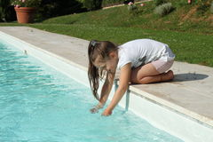 Pretty young girl playing with water at pool's edge Royalty Free Stock Image