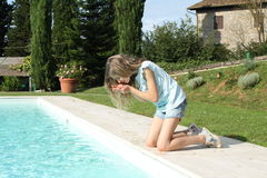 Pretty young girl playing with water at pool's edge Royalty Free Stock Images