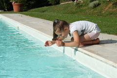 Pretty young girl playing with water at pool's edge Stock Images