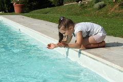 Pretty young girl playing with water at pool's edge Royalty Free Stock Photos