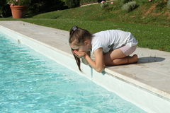 Pretty young girl playing with water at pool's edge Stock Photography