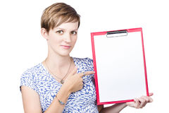 Pretty young girl pointing to paper on clip board Royalty Free Stock Image