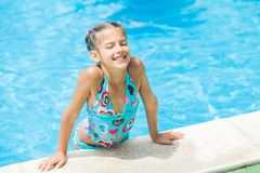 Pretty young girl at pool. Pretty young smiling girl near a side of the pool Royalty Free Stock Photo