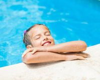 Pretty young girl at pool. Pretty young smiling girl near a side of the pool Royalty Free Stock Photography