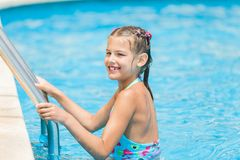 Pretty young girl at pool's edge Stock Images