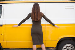 Pretty young girl posing near yellow bus in short sexy dress. Sexy Chick. Rear view from the back Royalty Free Stock Photos
