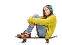 Pretty young girl posing with a skateboard, sitting on skate, l Stock Photo