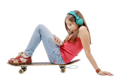 Pretty young girl posing with a skateboard, sitting on skate, l Stock Image