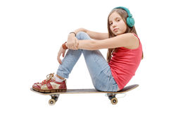 Pretty young girl posing with a skateboard, sitting on skate, li Royalty Free Stock Photos