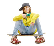 Pretty young girl posing with a skateboard, sitting on skate Stock Images
