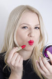 Pretty young girl puckered lips while putting on makeup Stock Photo