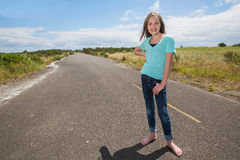 Pretty young girl on a quiet road Stock Photography