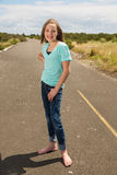 Pretty young girl on a quiet road Stock Image