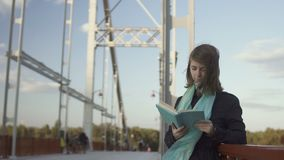 Pretty young girl read book on the bridge stock video footage