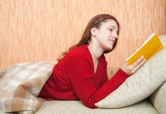Pretty young girl reading book on sofa Royalty Free Stock Image
