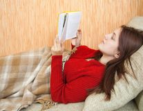 Pretty young girl reading book on sofa Stock Image