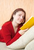 Pretty young girl reading book on sofa Stock Photography