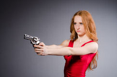 Pretty young girl in red dress with gun Stock Images
