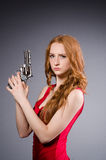 Pretty young girl in red dress with gun isolated. The pretty young girl in red dress with gun isolated on white Royalty Free Stock Photos
