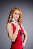 Pretty young girl in red dress with gun isolated Stock Photos