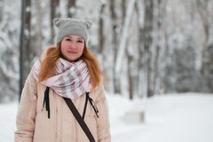 Pretty young girl with red hair in hat standing near snow pines in winter park royalty free stock image