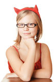Pretty young girl in red horns. Pretty young girl in glasses and red horns and red dress Stock Images