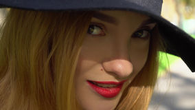 Pretty young girl with red lips in hat with wide brim. Closeup of pretty young girl with red lips in hat with wide brim looking at the camera and smiling stock images