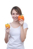 Pretty young girl with red and yellow peppers. Pretty young girl with two peppers orange and yellow Stock Image
