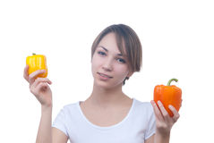 Pretty young girl with red and yellow peppers. Pretty young girl with two peppers orange and yellow Stock Images