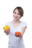 Pretty young girl with red and yellow peppers. Pretty young girl with two peppers orange and yellow Royalty Free Stock Images