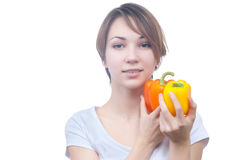 Pretty young girl with red and yellow peppers. Pretty young girl with two peppers orange and yellow Stock Photos