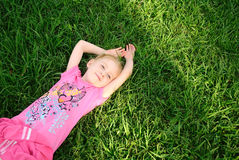 Pretty young girl relaxing on green grass Stock Photography