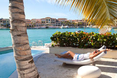 Pretty young girl resting at luxury villa. Happy beautiful brunet in sunglasses and white summer dress relaxing in luxury private villa, holidays in paradise stock images