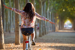 Pretty young girl riding bike in a forest. Stock Photos