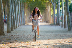 Pretty young girl riding bike in a forest. Stock Image