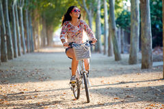 Pretty young girl riding bike in a forest. Royalty Free Stock Photos